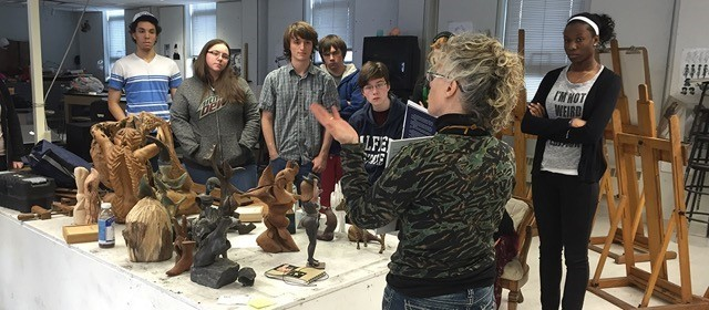 female instructor at front of classroom with students standing, pieces of art sitting on the table