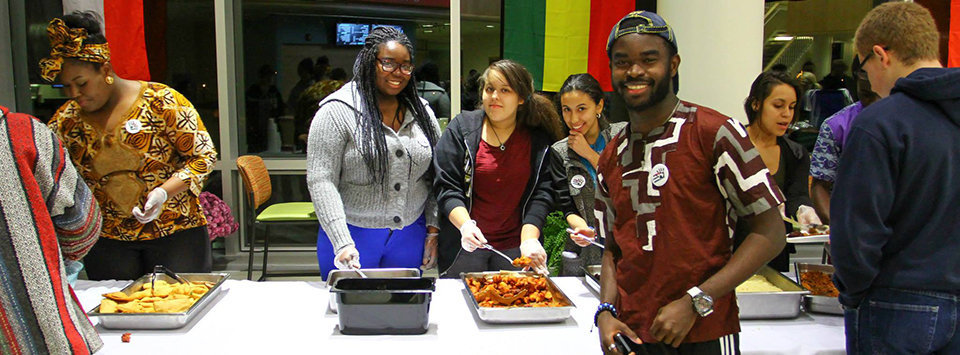 students serving food at a buffet line