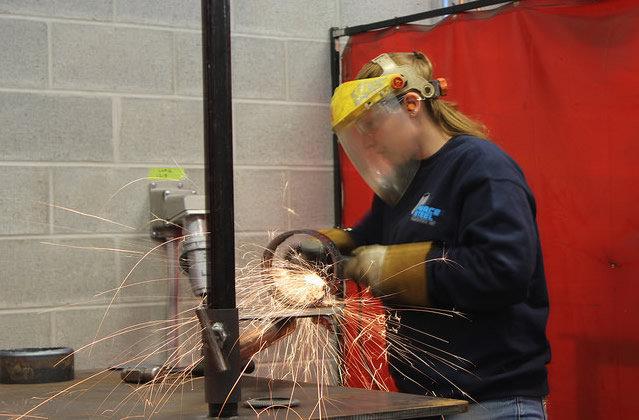 student wearing welding mask, welding
